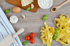 Preparation Italian Raw Homemade Pasta Tagliatelle Cooking. Baking Kitchen Table Wooden Different Ingredients Eggs Olive Oil Tomato Flour Basil Pepper Garlic Stock Photo