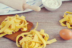 Preparation Italian Raw Homemade Pasta Tagliatelle Cooking. Baking Kitchen Table Wooden Different Ingredients Eggs Olive Oil Tomato Flour Basil Pepper Garlic Stock Photos