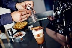 Preparation of latte macchiato with cinnamon Stock Image