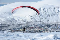 Preparation for launch. The paraglider pilot against a city and mountains prepares for launch Royalty Free Stock Images