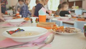 Preparation for a lunch break in the kindergarten. Children sit down at the table with cooked food. The Russian