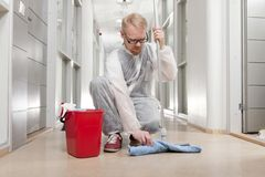 Preparation. Man in Overall Preparing Mop to Clean Office Corridor stock photography