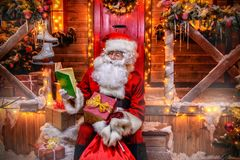 Preparation for x-mas. Santa Claus is preparing for Christmas, he reads a book with children`s desires. House of Santa Claus. Christmas decoration stock images