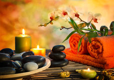 Preparation for massage in orange lights and black stones. Candles Stock Photo