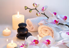 Preparation for massage with two towels, stones, candles and orchid. Preparation for massage in white with two towels, stones, candles and orchid Stock Photos
