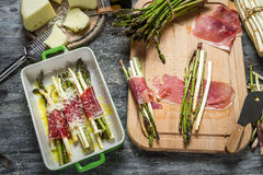Preparation meals made of asparagus, prosciutto and cheese royalty free stock photos