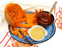 Preparation of a millet cereal with a pumpkin. The cut pumpkin, the millet, two pots,knife,wooden spoon,blue tray and towel on a white background Stock Photo