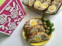 Preparation of minced meat rolls. As a stuffing boiled egg. Slices of the finished roll are on a plate with olives and greens. Preparation of minced meat rolls Stock Photography