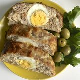 Preparation of minced meat rolls. As a stuffing boiled egg. Slices of the finished roll are on a plate with olives and greens. Preparation of minced meat rolls Stock Image
