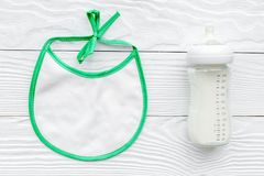 Preparation of mixture baby feeding with infant formula powdered milk in bottle with bib on white background top view Royalty Free Stock Photos