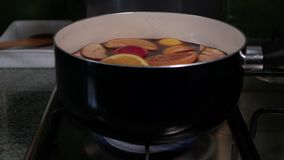 Preparation of mulled wine. Saucepan with red wine stands on the gas cooker and begins to boil. Steam from wine soar