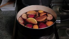 Preparation of mulled wine. Saucepan with wine stands on the gas cooker and begins to boil. Steam from wine soar over