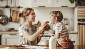 Free Preparation Of Family Breakfast. Mother And Child Son Cut Bread  And Eat Cookies With Milk In Morning Stock Images - 171972144