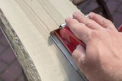 Preparation of an old wooden board by grinding with a hand sanding block stock photo