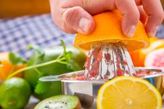 Preparation of orange grape or multivitamin juice, hands squeeze. Juice on a manual metal juicer surrounded by fresh tropical fruit Royalty Free Stock Photos