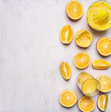 Preparation of orange juice squeezed fruit juicer on white wooden rustic background top view close up border ,place text Royalty Free Stock Photography