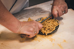 Preparation of passatelli fresh pasta using traditional tool Royalty Free Stock Image