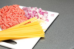 Preparation: pasta, mincemeat, onion, garlic with copy space Royalty Free Stock Image