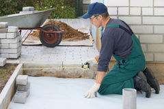 Preparation for a paving. The worker prepares a place for a paving Stock Photography