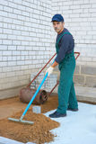 Preparation for a paving. The worker prepares a place for a paving Royalty Free Stock Photo