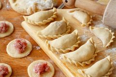 Preparation of pelmeni, ravioli, dumplings. With minced meat close up royalty free stock images