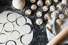 Preparation of pelmeni. Top view. Ingredients on black table. Traditional Russian cuisine. Royalty Free Stock Images