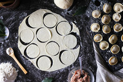Preparation of pelmeni. Top view. Ingredients on black table. Traditional Russian cuisine. Royalty Free Stock Image