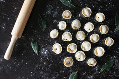 Preparation of pelmeni. Top view. Ingredients on black table. Traditional Russian cuisine. Stock Photos