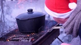 Preparation of pilaf on fire. Cooking soup. Nature, river, morning. Coldly. The guy in the hat of Santa. stock video footage