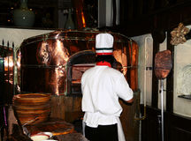 Preparation of a pizza. Cook at restaurant puts a pizza in an oven. Photo taken on: April 11th, 2012 in Thailand Stock Image