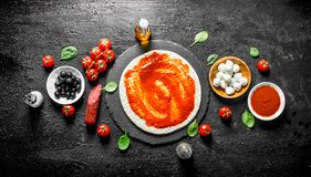 Preparation pizza. Dough with different ingredients for cooking pizza. On black rustic background royalty free stock photography