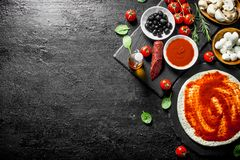 Preparation pizza. Dough with different ingredients for cooking pizza. On black rustic background royalty free stock photo