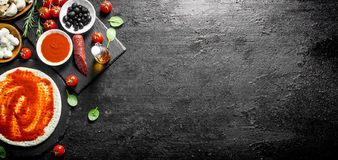 Preparation pizza. Dough with different ingredients for cooking pizza. On black rustic background stock photo