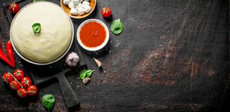 Preparation pizza. Dough with different ingredients for pizza. On dark rustic background stock photography