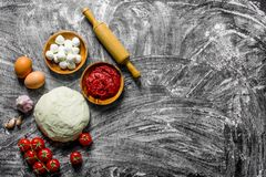Preparation pizza. Dough with sauce, mozzarella and tomatoes. On rustic background stock photography
