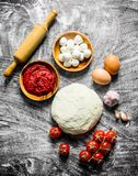 Preparation pizza. Dough with sauce, mozzarella and tomatoes. On rustic background stock image