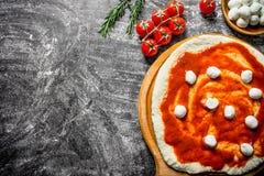 Preparation pizza. Dough with tomato paste and mozzarella. On rustic background royalty free stock photo