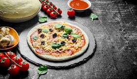 Preparation pizza. Dough with various ingredients for cooking pizza. On dark rustic background stock photography