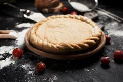 Preparation for pizza, flour and tomatoes on a round wooden board on a black wooden table Royalty Free Stock Photo