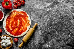 Preparation pizza. Rolled out dough with different pizza ingredients. On rustic background royalty free stock image