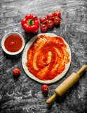 Preparation pizza. Rolled out dough with different pizza ingredients. On rustic background stock photos