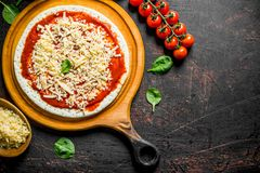 Preparation pizza. Rolled out dough with tomato paste, cheese and cherry tomatoes. On dark rustic background stock image