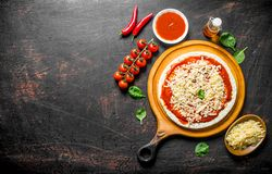 Preparation pizza. Rolled out dough with tomato paste, cheese and cherry tomatoes. On dark rustic background stock photos