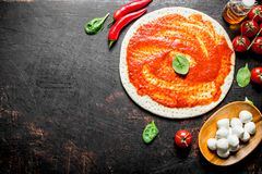 Preparation pizza. Rolled out dough with tomato paste, chili pepper and mozzarella. On dark rustic background royalty free stock photography