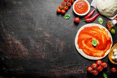 Preparation pizza. Rolled out dough with tomato paste, chili pepper and mozzarella. On dark rustic background royalty free stock photo