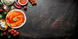 Preparation pizza. Rolled out dough with tomato paste, chili pepper and mozzarella. On dark rustic background royalty free stock images