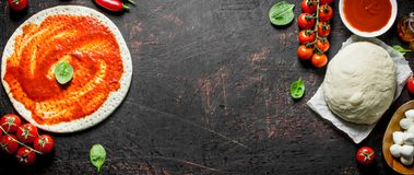 Preparation pizza. Rolled out dough with tomato paste. On dark rustic background royalty free stock image