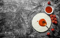 Preparation pizza. Rolled out dough with tomato paste and fresh tomatoes. On rustic background royalty free stock photo