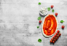 Preparation pizza. Rolled out dough with tomato paste, mozzarella and spinach. On white wooden background stock photo