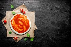 Preparation pizza. Rolled out dough with tomato paste. On black rustic background royalty free stock photography